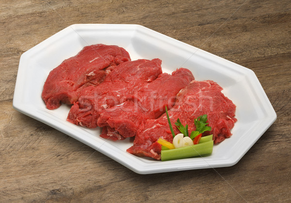 Raw meat selection on wooden cutting board. Stock photo © paulovilela