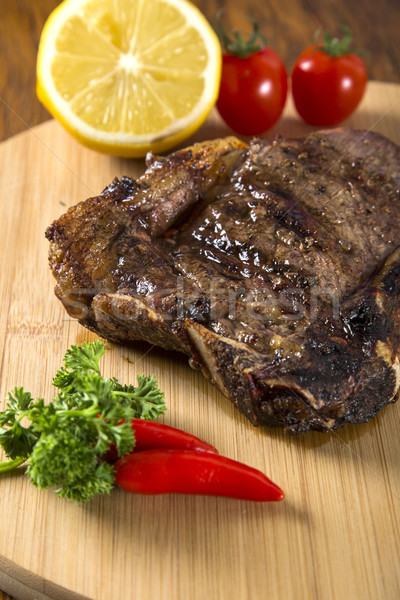 Grilled meat ribs on white plate with tomatoes chives and dark h Stock photo © paulovilela
