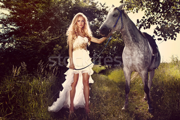 Stock photo: Beautiful young bride with horse in garden.
