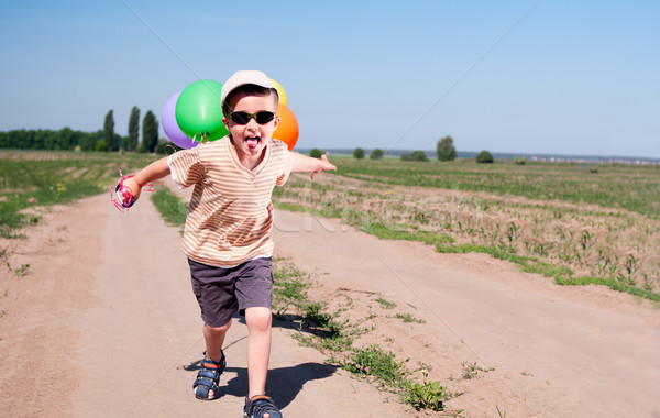 Little boy with colorful balloons running the country road Stock photo © pekour