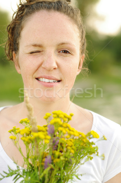 Mischievous redhead woman with bouquet wink Stock photo © pekour