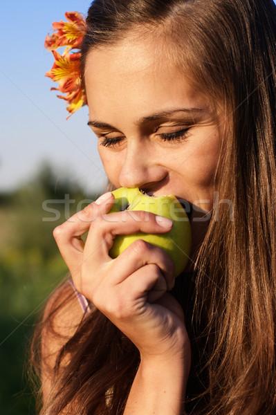 Fiatal lány falat alma virág haj gyönyörű lány Stock fotó © pekour