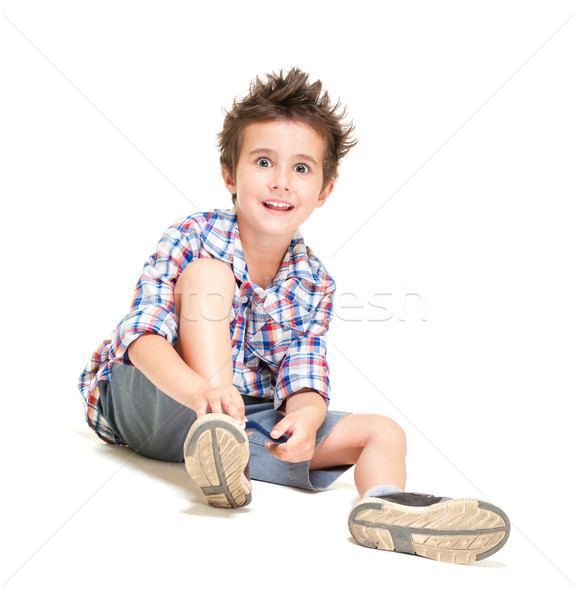 Naughty hairy little boy in shorts and shirt putting on shoes Stock photo © pekour