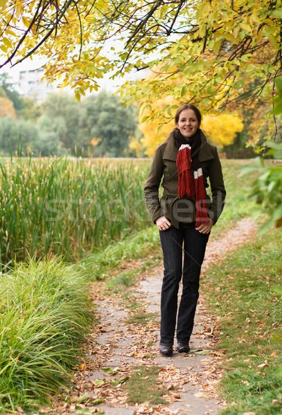 Kadın yürüyüş park sonbahar gülümseme Stok fotoğraf © pekour
