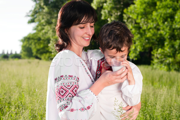 Mother and son in traditional ukrainian shirt drink milk outdoor Stock photo © pekour