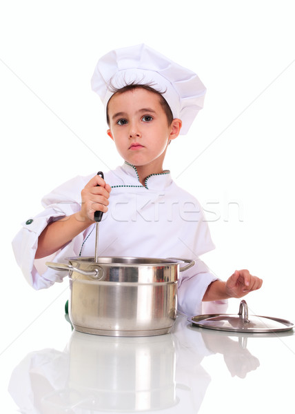 Little boy chef in uniform with ladle stiring in the pot Stock photo © pekour