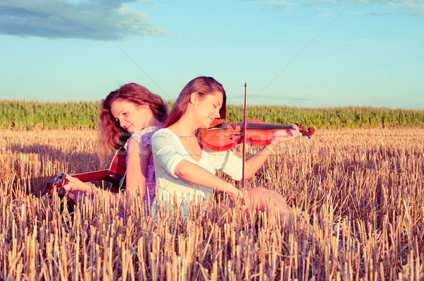Two young women playing guitar and violin outdoors. Split toning Stock photo © pekour