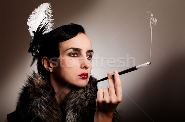 Retro woman in fur with cigarette mouthpiece Stock photo © pekour