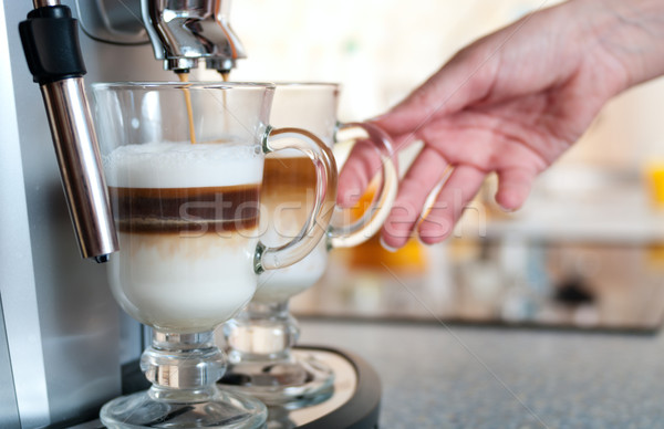 Glasses fileed with capuccino in cofee machine with womans hand Stock photo © pekour