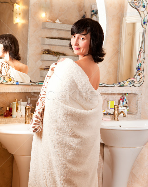 Smiling woman in bathroom by the mirror wrapped in mantle Stock photo © pekour