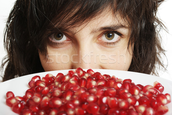 Beautiful woman holds pomegranate berries in white plate Stock photo © pekour