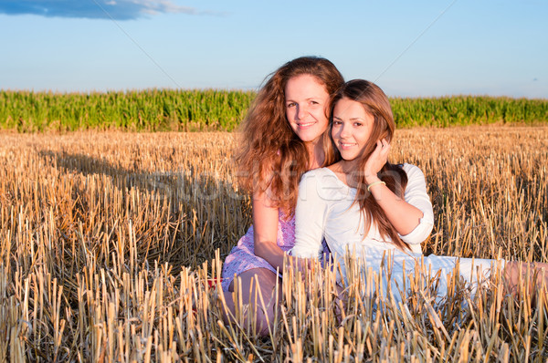Two girls friends lean each another on summer field Stock photo © pekour
