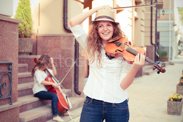 Women strings duet playing violin and cello on the street Stock photo © pekour