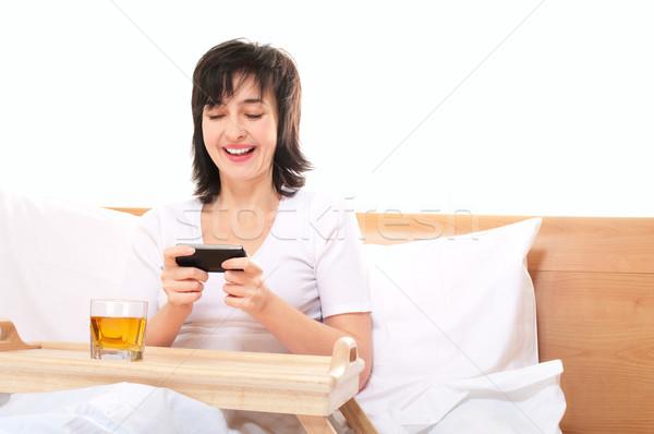 Vrouw video games mobiele smartphone bed geïsoleerd Stockfoto © pekour