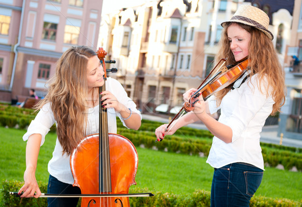 Two women strings duet playing violin and cello in square Stock photo © pekour