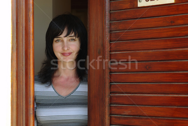 Beautiful woman welcomes at the door Stock photo © pekour