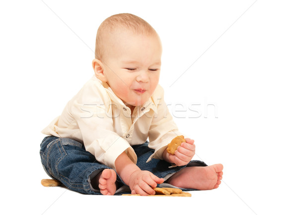 Happy laughing baby in jeans eating cracker Stock photo © pekour