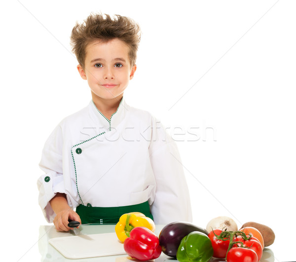 Stock photo: Little boy chef in uniform with knife cutting vegetables