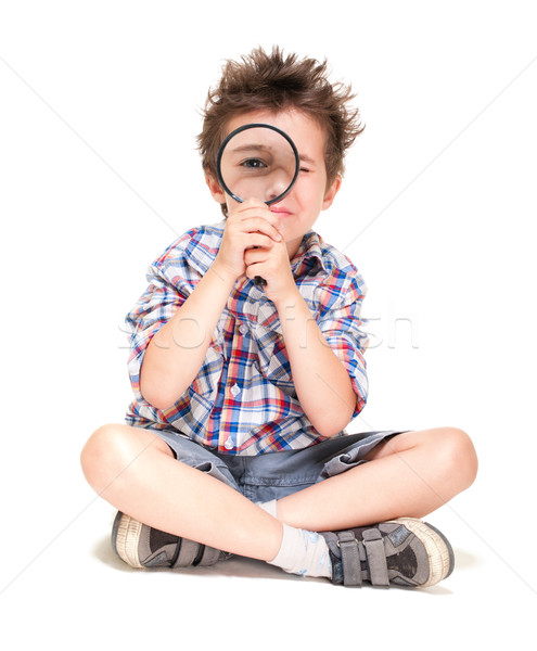 Attentive little boy with weird hair researching using magnifier Stock photo © pekour
