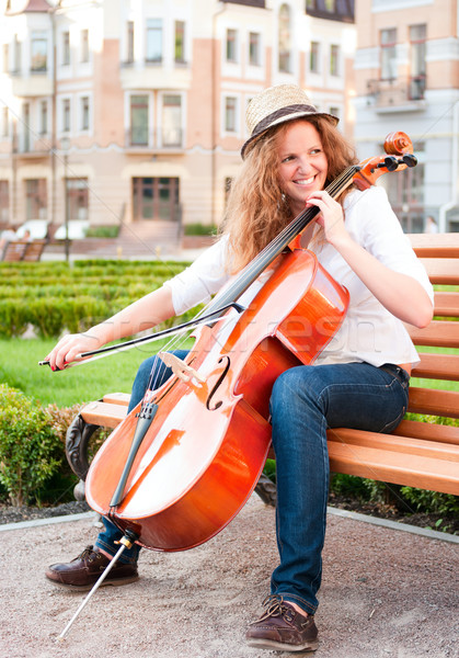 Woman playing cello on the bench in square Stock photo © pekour