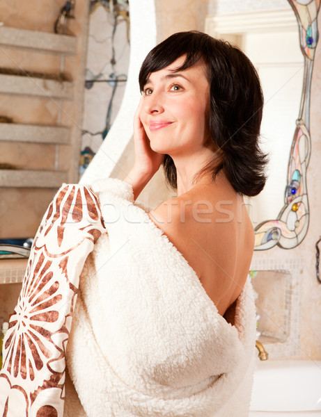 Smiling woman in bathroom wrapped in mantle Stock photo © pekour