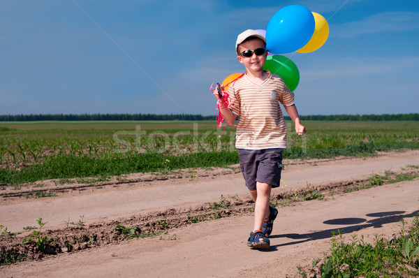 Little boy with colorful balloons walking the country road Stock photo © pekour