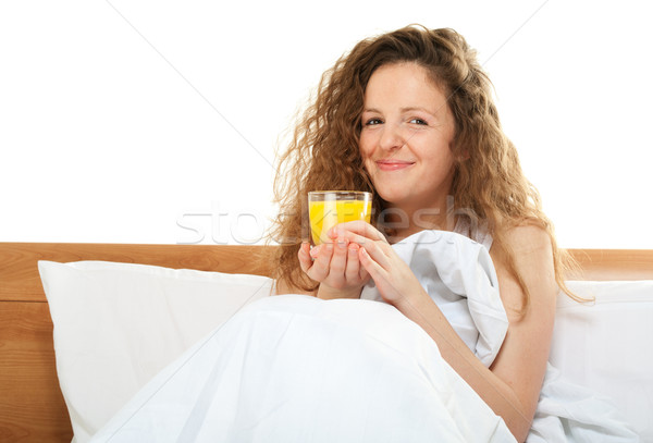 Happy redhead woman in bed with glass of orange juice Stock photo © pekour