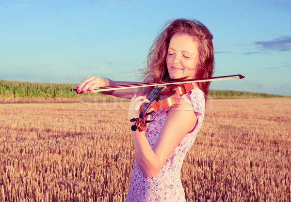 Redhead woman playing violin outdoors on the field. Split toning Stock photo © pekour