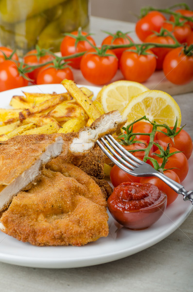 Big Chicken schnitzel with homemade chilli french fries Stock photo © Peteer
