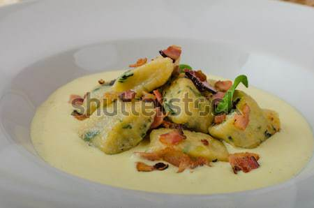 Spinach gnocchi with parmesan sauce topped with bacon Stock photo © Peteer