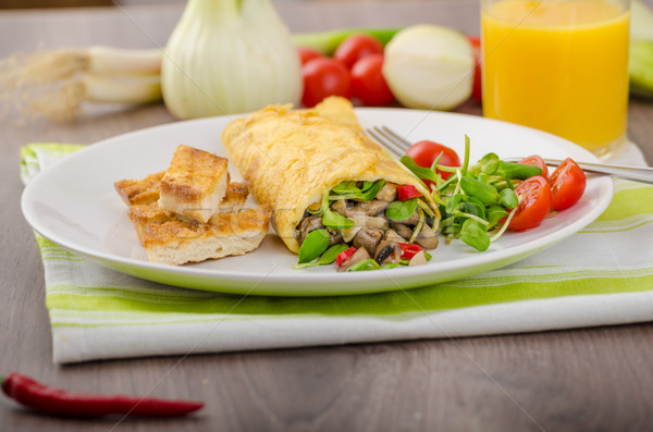 Omelette stuffed with mushrooms and microgreens Stock photo © Peteer