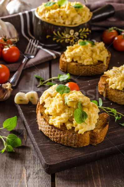 Scrambled eggs with herbs and garlic on toasted bread Stock photo © Peteer
