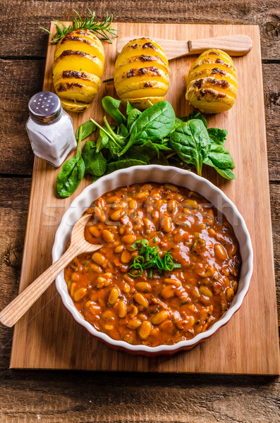 Spicy cowboy beans with hassleback potatoe with herbs Stock photo © Peteer