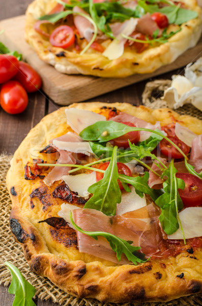 Italian pizza with parmesan cheese, prosciutto and arugula Stock photo © Peteer