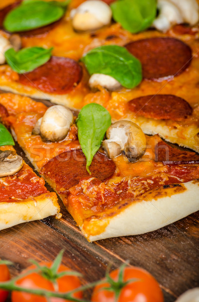 Rustic pizza with salami, mozzarella and spinach Stock photo © Peteer