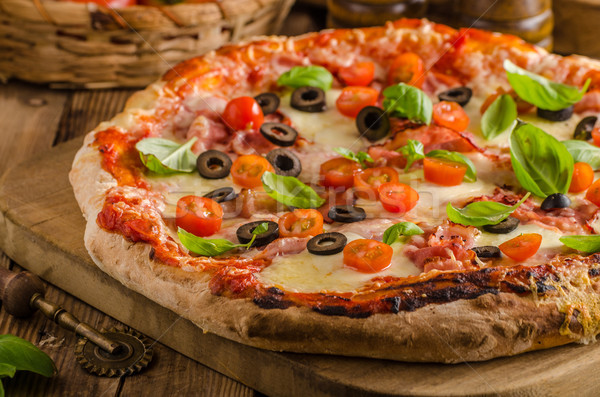Rustic pizza with tomato, cheese, salami Stock photo © Peteer