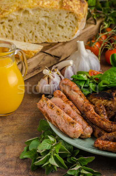 Grilled chicken wings and sausages Stock photo © Peteer