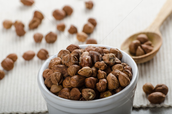 Hazelnuts in a bowl, spoon on the towel Stock photo © Peteer