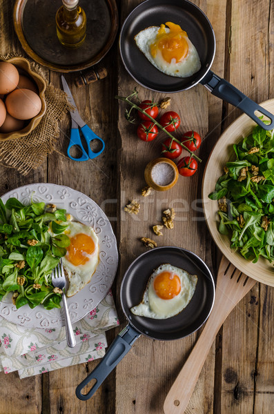 Fried eggs with salad and nuts Stock photo © Peteer