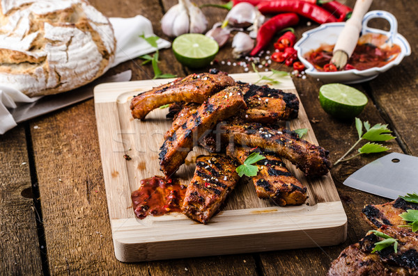 Grilled Spareribs in spicy marinade with beer and rustic bread Stock photo © Peteer