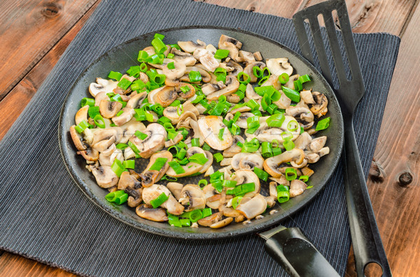 Fried mushrooms with spring onion on pan Stock photo © Peteer