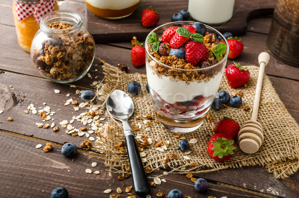 Yogurt with baked granola and berries in small glass Stock photo © Peteer