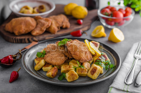 Schnitzel original with lemon and gnocchi fried Stock photo © Peteer