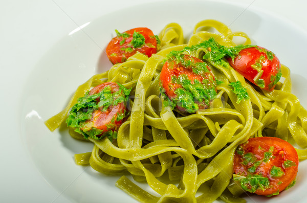 Stock photo: Pasta with basil pesto and pine nuts, cherry tomatoes