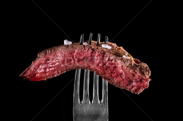 Beef meat rare on fork black background Stock photo © Peteer