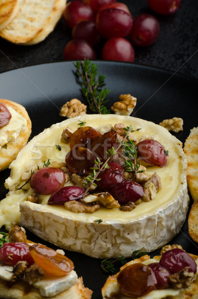 Brie cheese baked with nuts and grapes Stock photo © Peteer