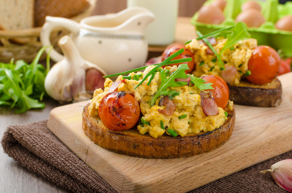 Scrambled eggs witch bacon, herbs and tomato Stock photo © Peteer
