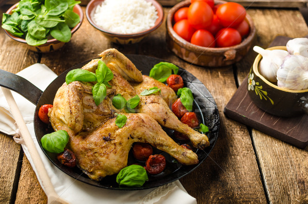 Chicken baked with tomatoes and basil on iron pan Stock photo © Peteer
