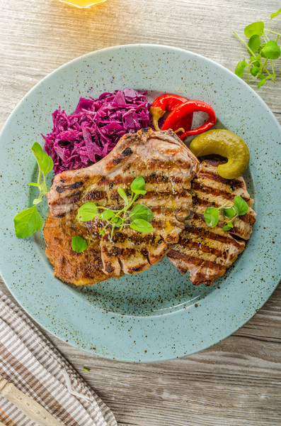 Stock photo: Grilled pork chops with herbs and garlic, potato pancakes