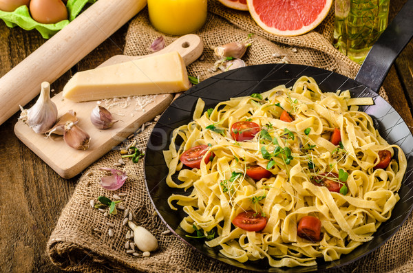 Stock photo: Semolina pasta with roasted garlic, sprinkled microherbs